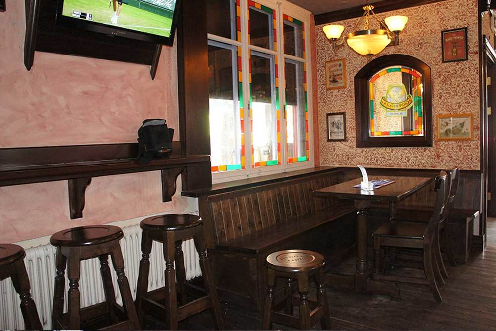 Duffy O'Tooles authentic Irish pub design - interior view of stained glass windows and adorned mirrors.