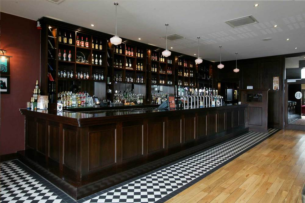 Bewley's hotel bar design - dark wood bar designed by Guinness approved designers