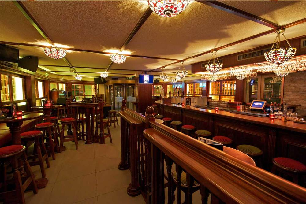 Papperla authentic Irish pub design - interior view of high wooden tables and stools