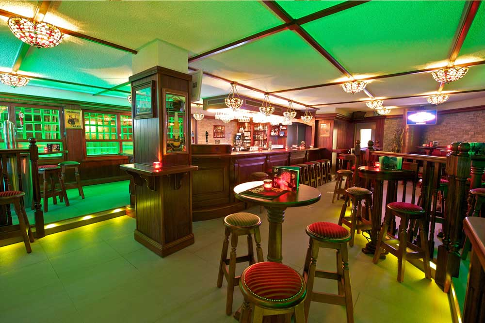 Papperla authentic Irish pub design - interior view of seating with green lighting, high wooden tables and wooden stools