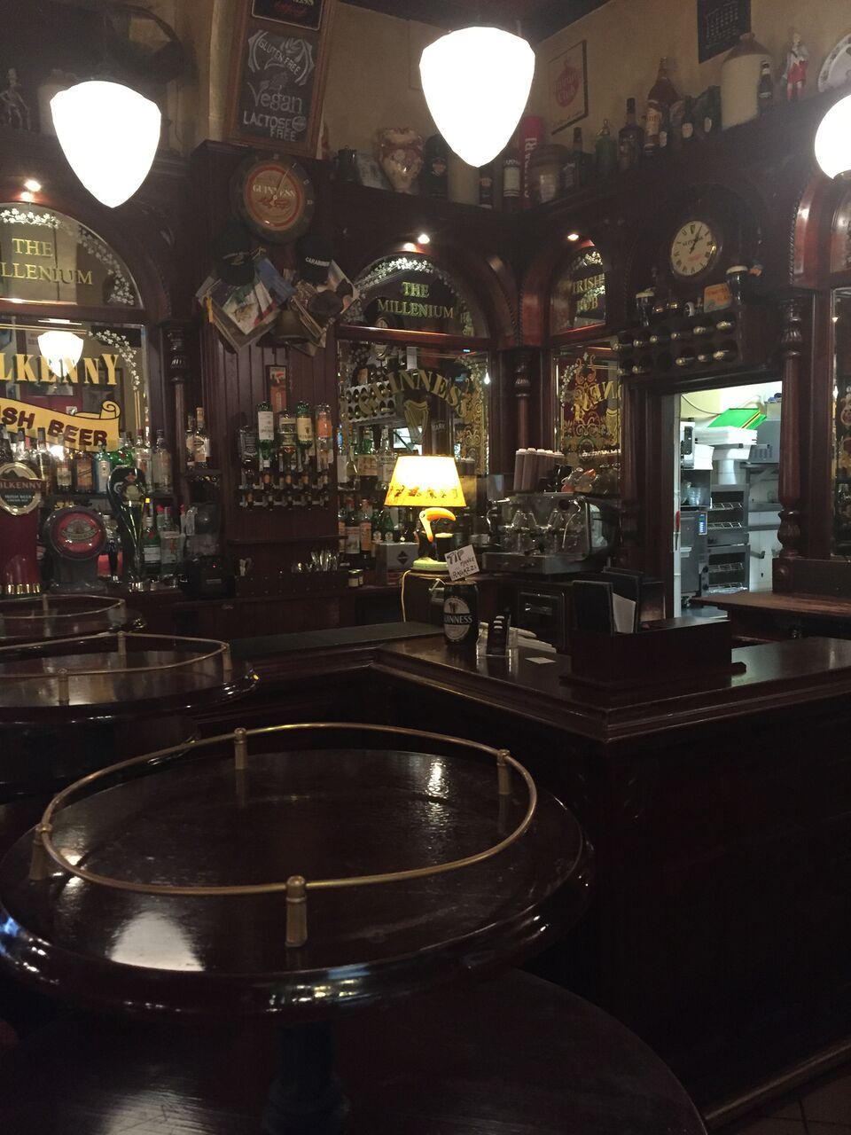 Victorian Irish Pub Design - Interior view of dark wooden furnishings and soft lighting.