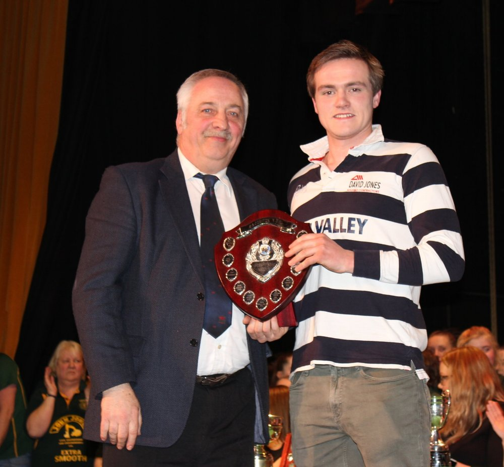 Conor Price, Edw Valley YFC being presented the 'Knighton YFC Shield' for third place Pantomime by David Powell, FUW