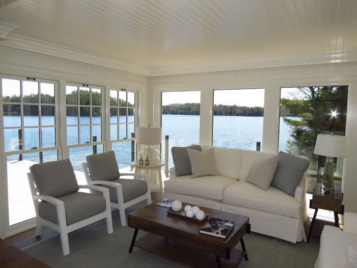 Living room of boathouse looking out at view of the lake