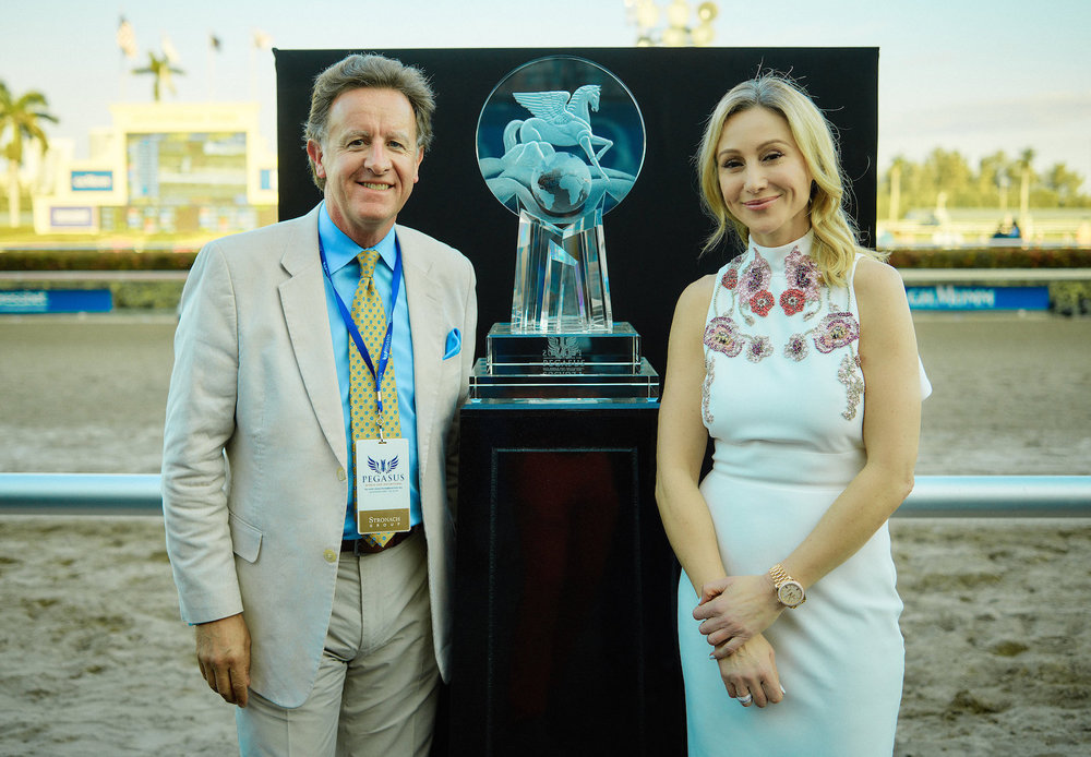 "The Pegasus World Cup Invitational thoroughbred trophy is seen track side with artist Mark Raynes Roberts and Belinda Stronach, Chairman & President, who commissioned the crystal masterpiece with her father Frank Stronach, Founder & Honourary Chairman, of The Stronach Group. The magnificent crystal trophy weighs 112lbs and was designed and  hand-carved by the crystal artist for the World's richest horse race which now has a purse of $16 million for the January 27, 2018 running at Gulfstream Park, in Florida. The inaugural race was won by the super horse ""Arrogate"" of Juddmonte Farms Inc, from Lexington, Kentucky, which is owned by Saudi Royal family member, Prince Khalid bin Abdullah Al Saud."