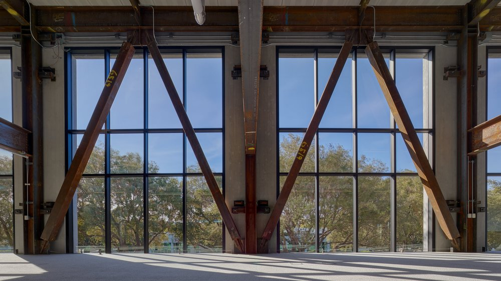 The building's infrastructure is a significant design feature, setting the tone for the interiors. The exposed raw steel structure retains the markings from fabrication, without layers of potentially toxic fireproofing.