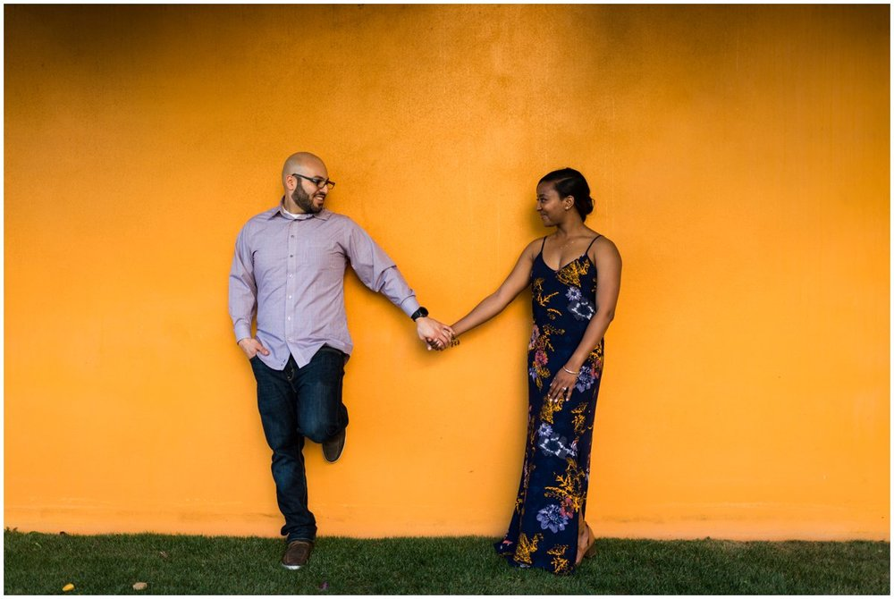 Interracial Couple Engagement Photos in Mesa with a colorful wall.