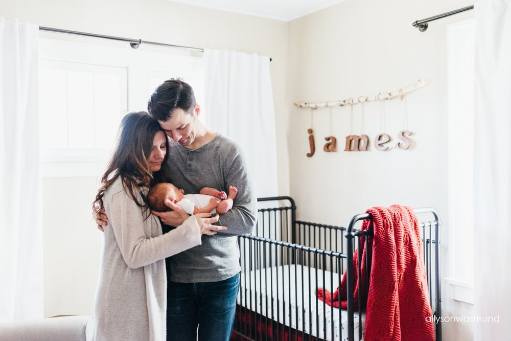 A new family of three standing in their son's nursery in Minneapolis, Minnesota.