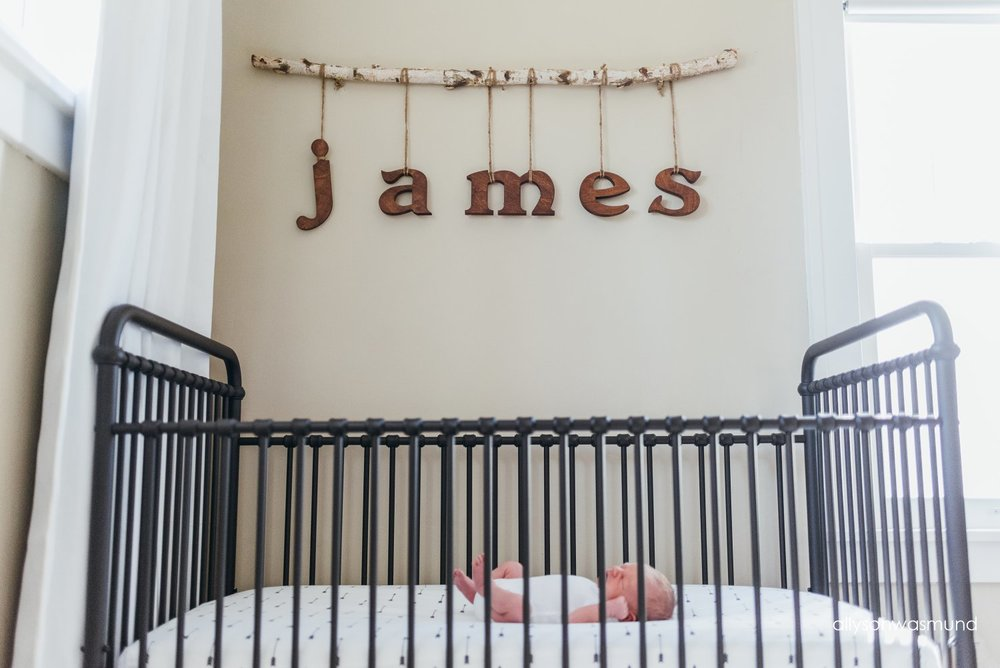 A newborn baby boy sleeping in his crib during his lifestyle newborn session in Minneapolis, Minnesota.