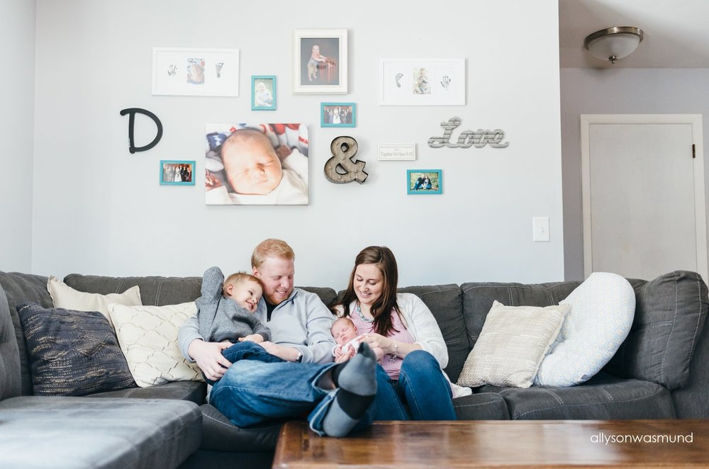A new family of four sitting in their Bloomington, Minnesota living room during their in-home lifestyle newborn session with Allyson Wasmund Photography.