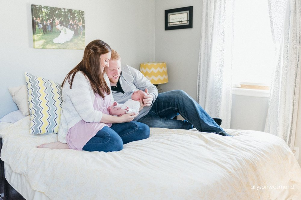 Mom, dad and baby girl sitting on a bed in their Bloomington, Minnesota home during their in-home newborn session.