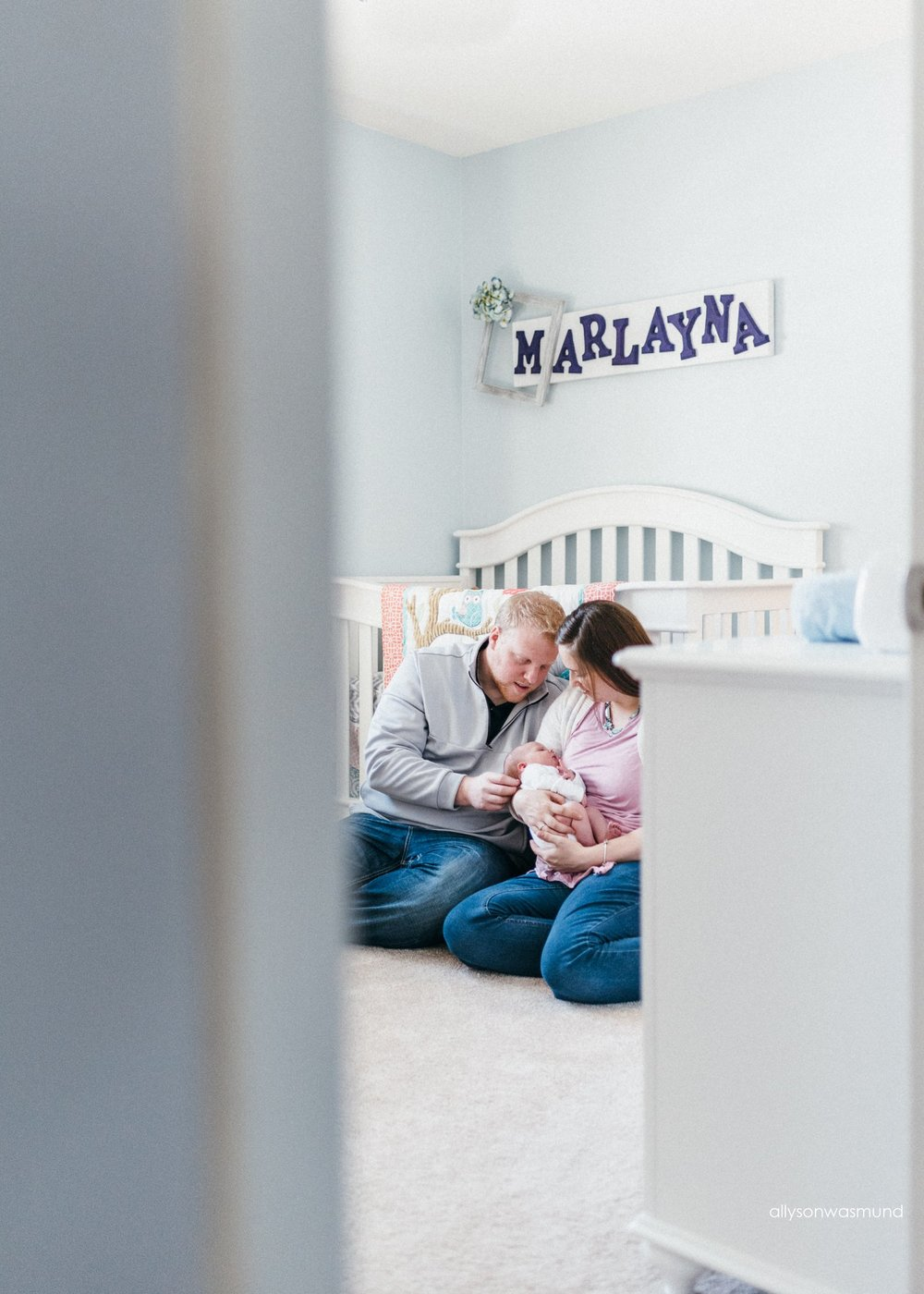 Mom, dad and baby girl sitting in the nursery on the floor of their Bloomington, Minnesota home during their lifestyle newborn session.