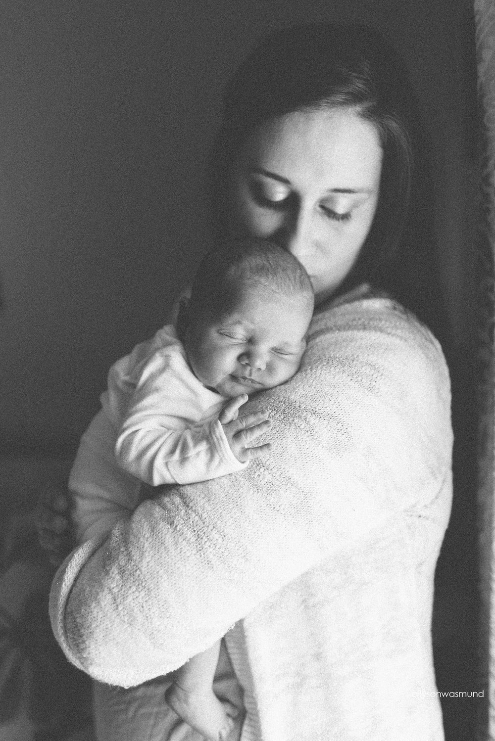 Mom holding her new baby girl by a window in their Bloomington, Minnesota home during their lifestyle newborn session.
