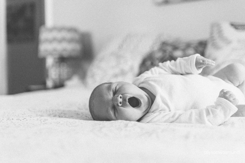 Baby girl laying on her parent's bed yawning during her in-home lifestyle newborn session.