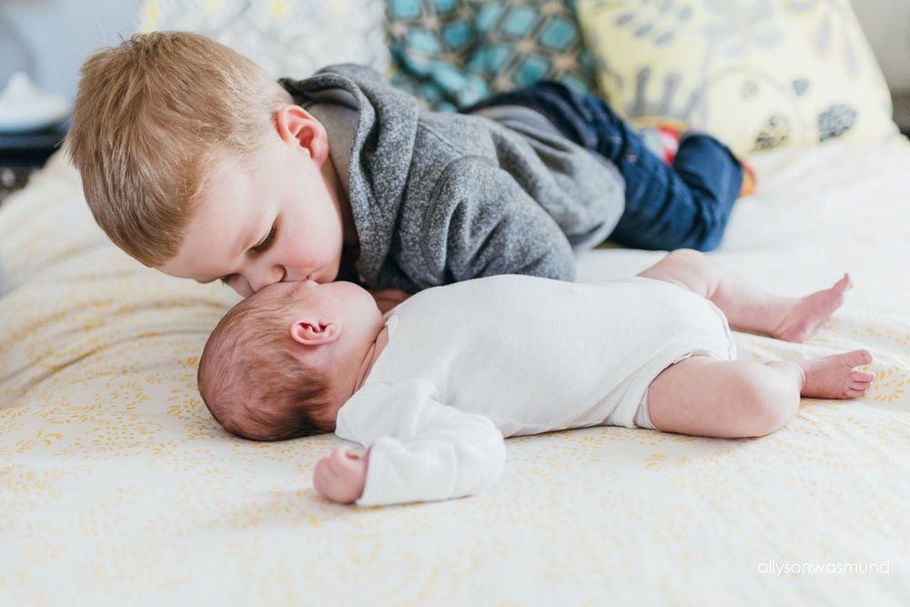 Brother kissing the top of his baby sister's head during their in-home newborn session.