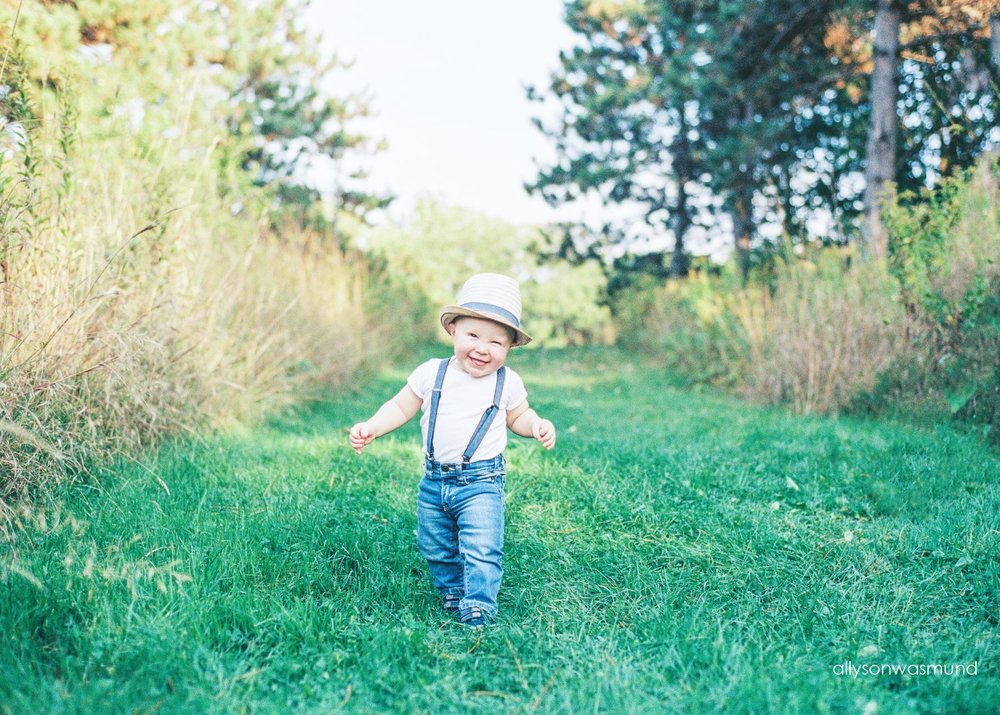 Adorable Asher with a big smile during his outdoor baby milestone session, captured on film.