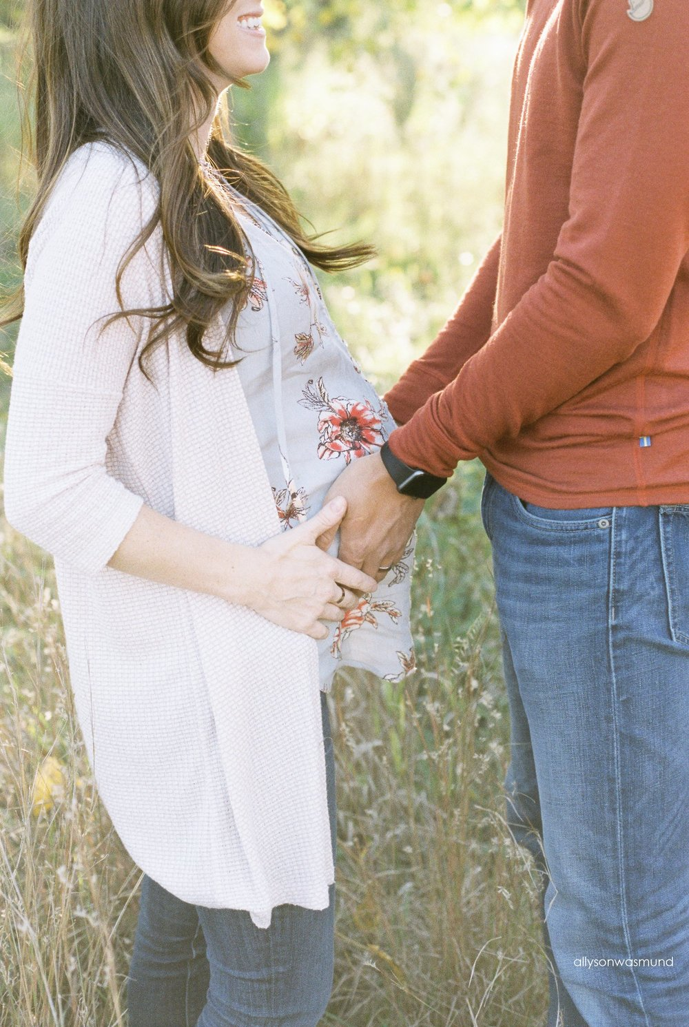 A happy couple smiles as they are photographed at their outdoor film maternity session.