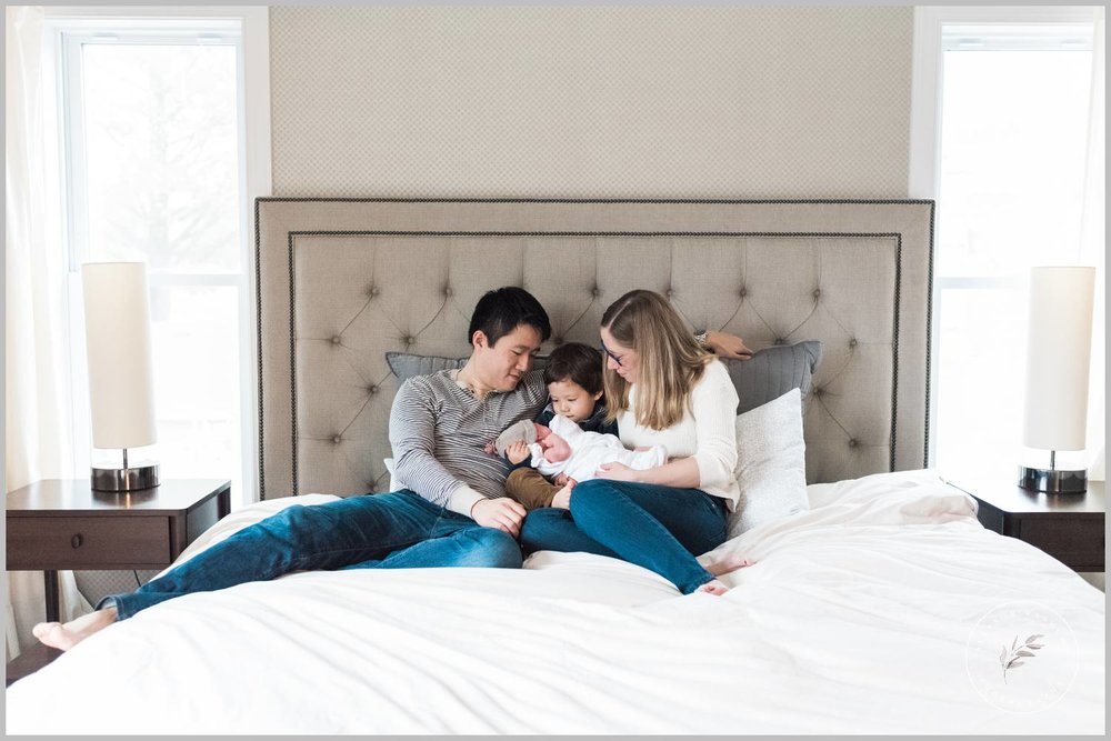 A new family of four sits on a bed in their St. Paul MN home admiring newborn Kayli.