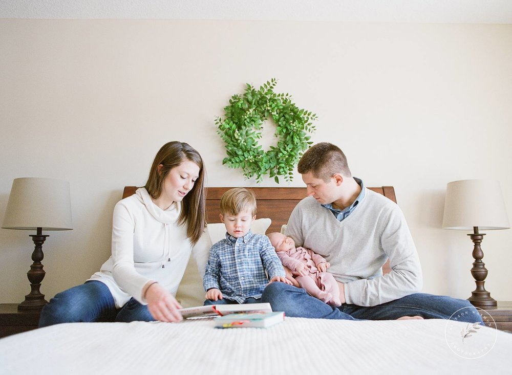 A new family of four sits on a bed during their newborn session in Forest Lake, Minnesota with Allyson Wasmund Photography.