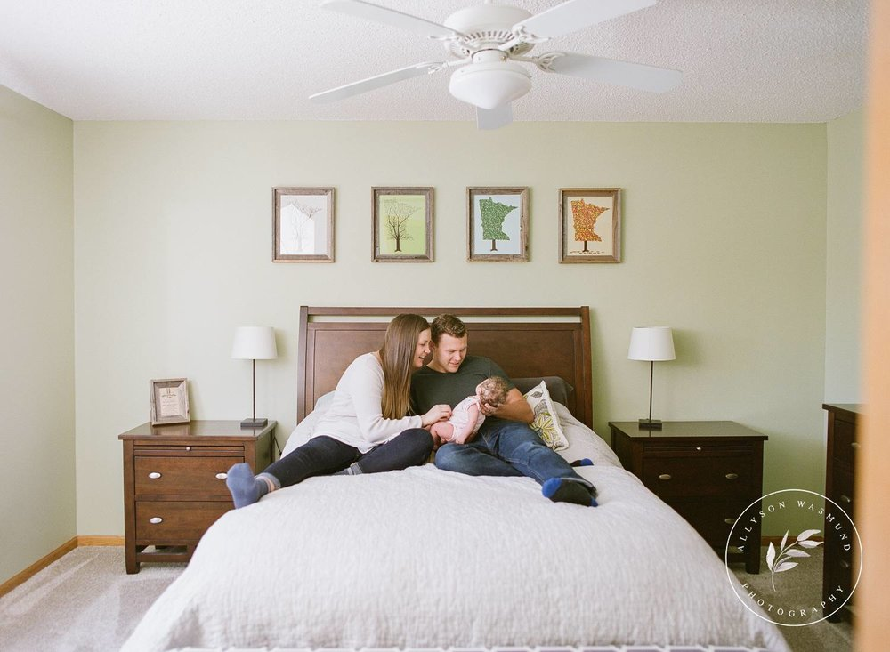A new family of three relaxes on their bed looking down at their baby girl during their in-home newborn session with Allyson Wasmund Photography.