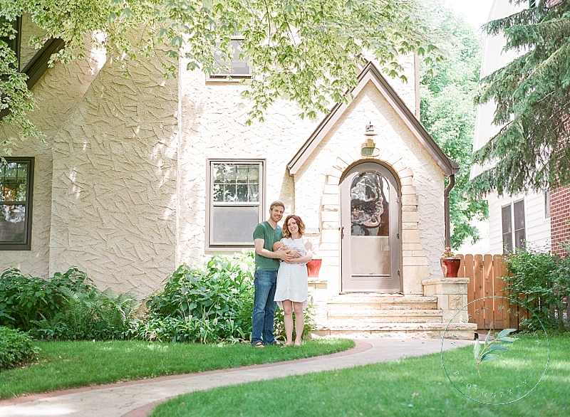 A new family of three stands outside of their St. Paul MN home at the end of their at home newborn photography session.