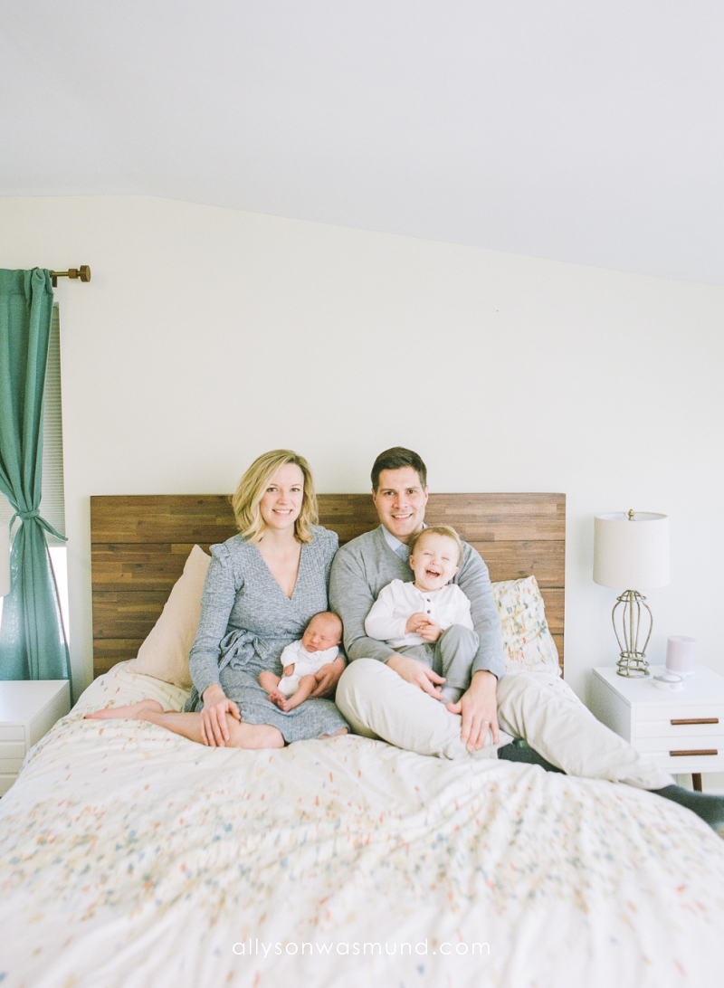 A new family of four sits on a bed in their St. Paul, Minnesota home during their lifestyle newborn session with film photographer, Allyson Wasmund.