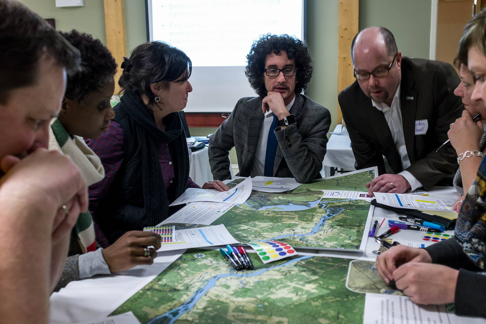 Participants denote hazards, vulnerabilities, and resiliency measures during a table top map-based exercise, in Fredericton, February 2017.