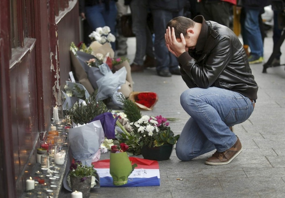A man kneels next to a memorial outside Le Carillon restaurant the morning after a series of deadly attacks in Paris. (Christian Hartman/Reuters)