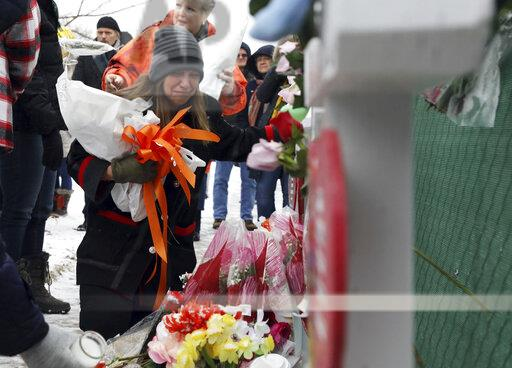 People pray at a makeshift memorial Sunday, Feb. 17, 2019, in Aurora, Ill., near the Henry Pratt Co. manufacturing facility where five were killed on Friday. (Photo by AP Photo/Nam Y. Huh)