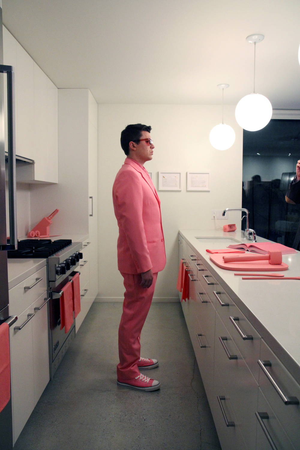 "The Schauss Kitchen (Cooking)  Baker-Miller Pink painted kitchen objects, Baker-Miller Pink ""cookbook,"" Baker-Miller Pink color therapy glasses, custom Baker-Miller Pink suit Installation dimensions variable, performance duration 15 minutes Marine Contemporary Art Salon, Venice, CA. 7:30pm, February 9th, 2013 Photo Courtesy of Sean Flaherty"