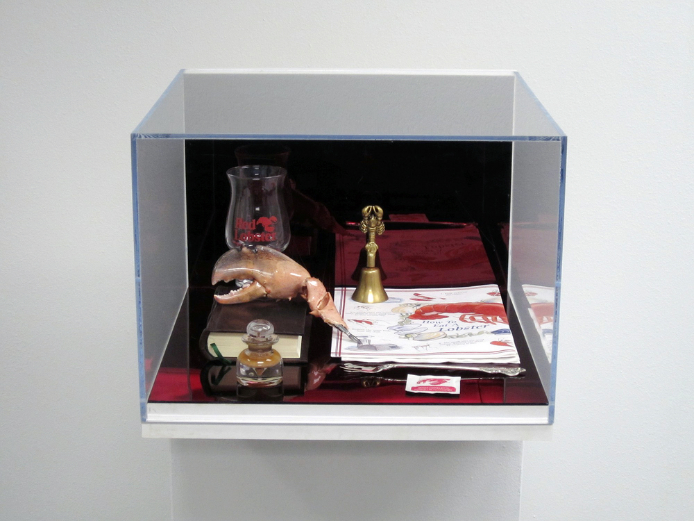 "How to Eat Lobster (Ritual)  2011 Wall mounted plexi-glass and wood vitrines, contents: red mirrored plexi-glass, ""Red Lobster"" drinking glass, brass bell, paper placemat and napkin, leather book, moist towelette, sterling silver lobster fork, taxidermy lobster claw quill pen, homemade lobster ink with inkwell dimensions variable"