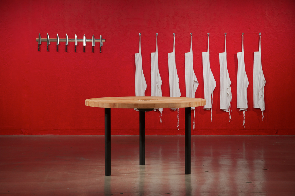 The Pleasures of the Table  2012 maple butcherblock, mixing bowl, metal, 8 chefs knives, magnetic knife rack, 8 aprons, metal hooks Dimensions variable