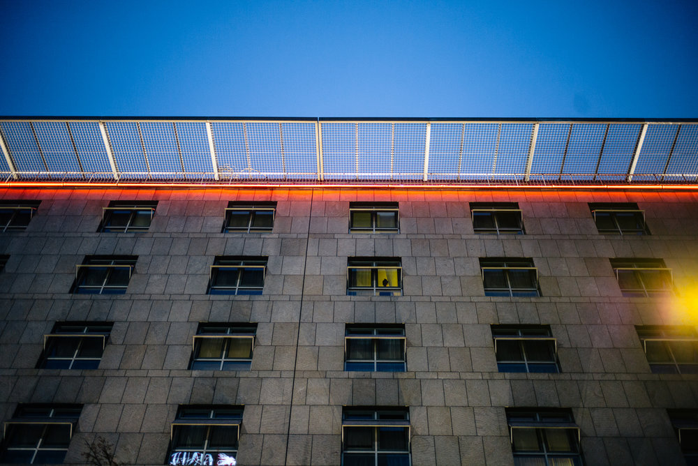 A spectator watches from her apartment above the protest.