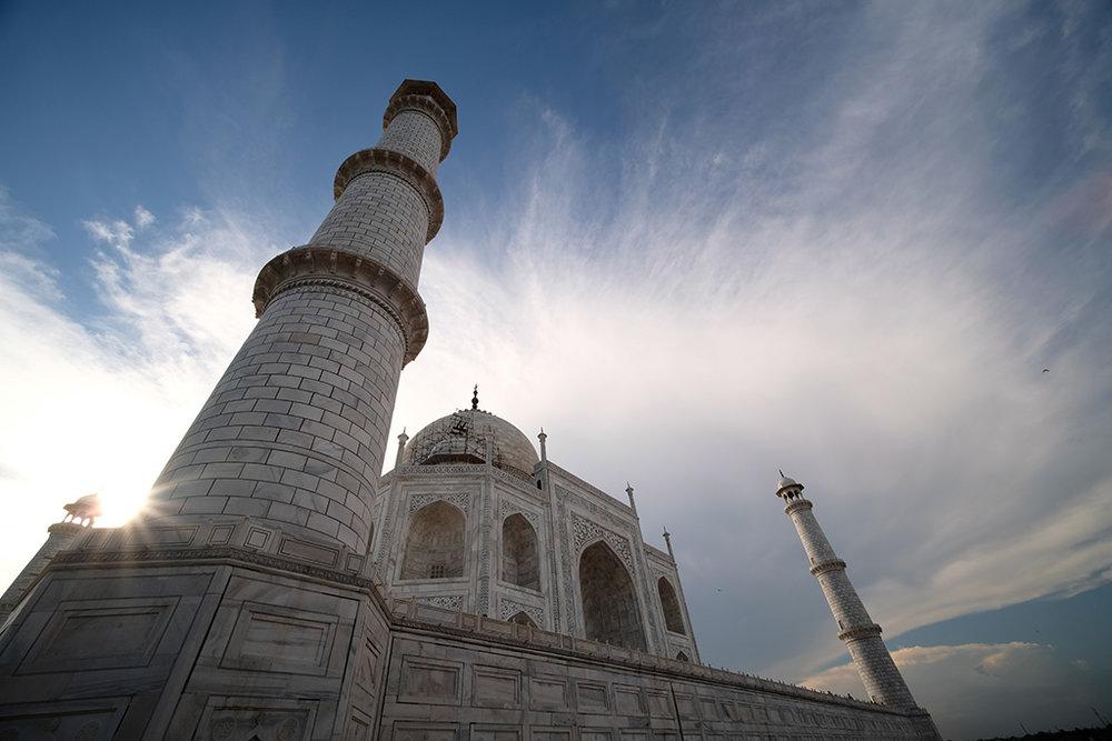 The sun peeking from behind the Taj Mahal