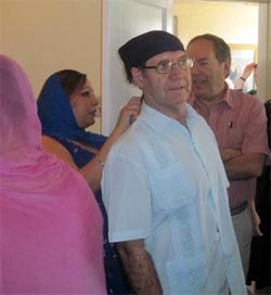 Respect means being open to the customs of individual worship sites. Here Rob Hankinson waits his turn as Paul McKenna, North American Interfaith Network trustees from Canada, has a headscarf tied on his head before joining worship at the Sikh gurdwara in Phoenix, Arizona.
