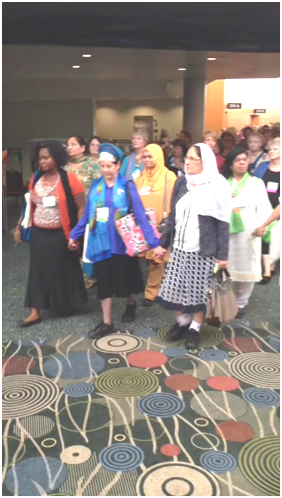 Despina Namwembe, Elana Rozenman, and Siham Halabi lead the Multi-faith Women's Walk for Peace at the Parliament of the World's Religions last October. – Photo: Twitter, Paul Rauschenbush