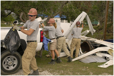 Volunteers from AmeriCorp, a government-funded agency, pile debris from a yard into their truck to take to a pick-up location. – Photo: Wikipedia, Marvin Nauman/FEMA
