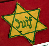 The yellow 'badge' required of Jews by Nazis in France. – Photo: Wikipedia, Rama