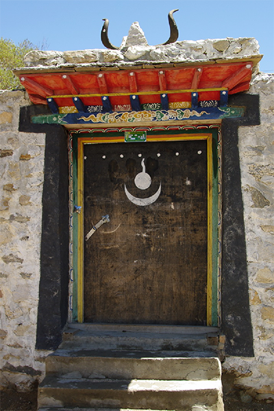 A door in Tibet with sacred symbols from the Bon religion. – Photo: Wikipedia