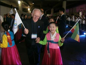 Marcus takes the hand of a South Korean girl at the Peace Summit