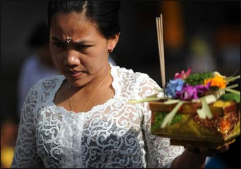 A Balinese woman carries an offering as she celebrates the religious festival of Galungan at a temple in Denpasar, on Indonesia's tourist island of Bali on October 23, 2013. – Photo: AFP