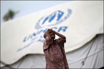 A girl from the Pauktaw township stands in front of her family's shelter in a Rohingya internally displaced persons (IDP) camp outside Sittwe. – Photo: Soe Zeya Tun, Reuters