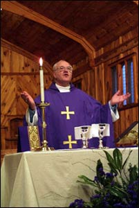 George Carey, former archbishop of Canterbury, celebrates Communion during a meeting of the Anglican primates in North Carolina in 2001. – Photo: James Rosenthal, Anglican Communion News Service