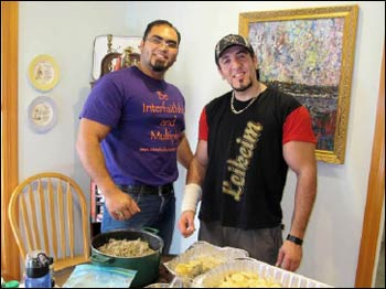 Tony (l.) and Ahmad pose in front of the Jordanian meal they've prepared.