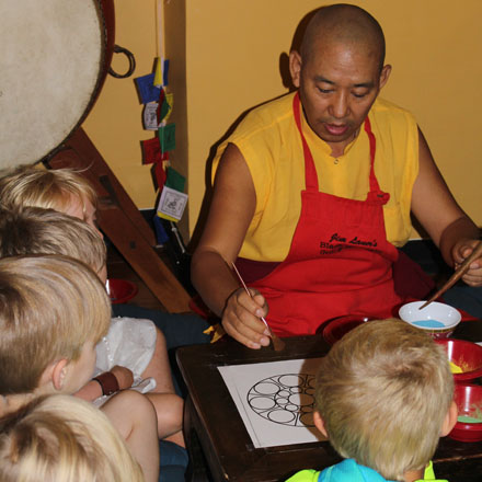 Kids learn about the construction of sand mandalas from a Tibetan Buddhist lama. – Photo: Vicki Garlock