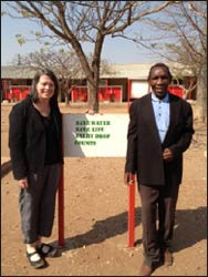"The author visiting Sam Rahube, former headmaster, at their school in Botswana, where the taps sometimes run dry. The sign reads: ""Save Water Save Life Every Drop Counts."""
