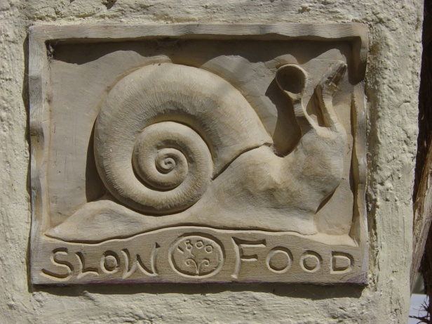 The snail was chosen to be the patron and symbol of the slow food movement. The plaque here was found on a wall outside a restaurant in Santorini, Italy .