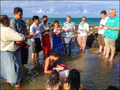 From the December 2014 story by Aaron Stauffer: People gather to pray in the sea to express solidarity with communities affected by sea-level rise. – Photo: Twitter/OurVoices2015