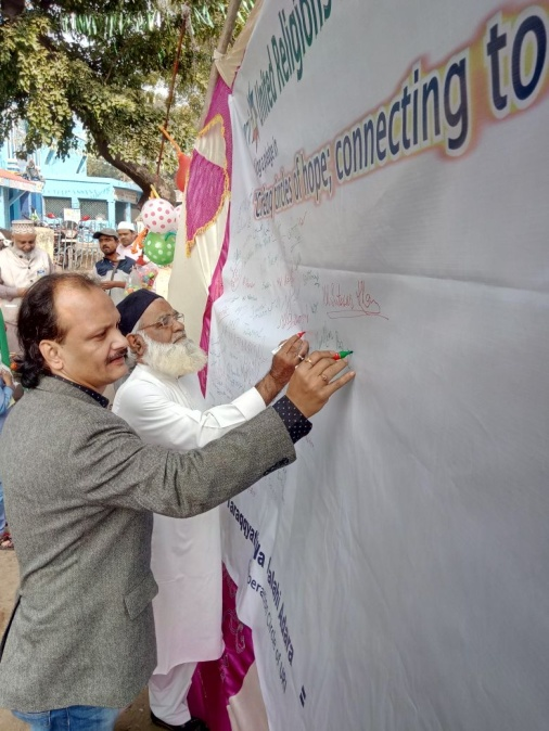 Biswadeb Chokraborty (l.) and a Muslim leader signing the pledge to support interfaith harmony. – Photo: URI