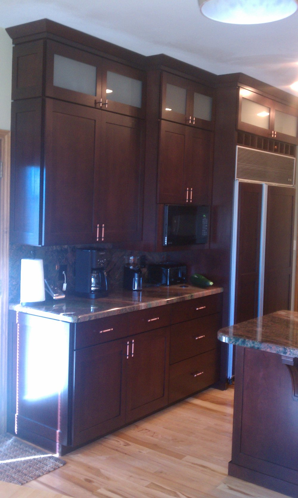 Shaker kitchen with frosted glass doors, full overlay spacing, crown moulding, full size base boards, and shaker side panels.