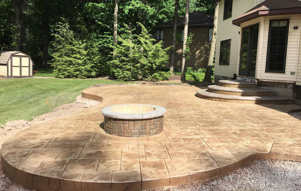 Large Ashlar Slate stamped patio, custom designed landing/steps along with matching 4 diameter fire pit. Thyme integral color w/ 70% Buff Tan & 30% Chestnut releases.